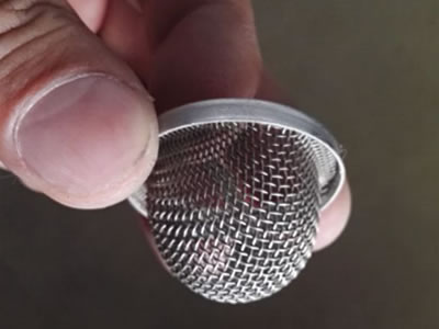 Two fingers are pinching a piece of bend edge suction strainer.