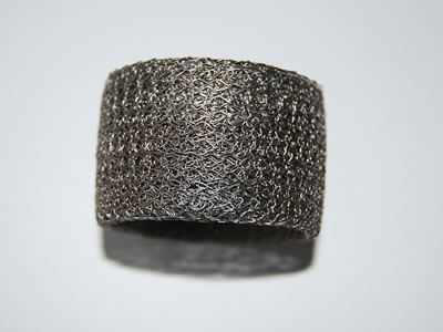 A round small compressed knitted wire mesh filter.