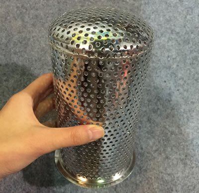 A hand is holding a perforated cylinder wire cloth strainer.