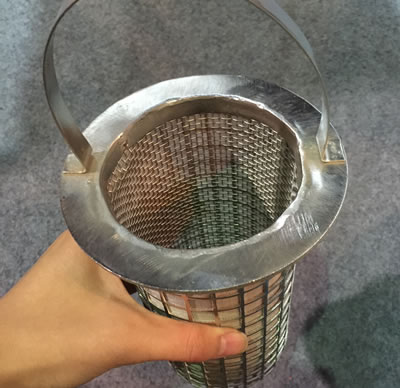 The hand is holding a cylinder wire cloth strainer with a handle.