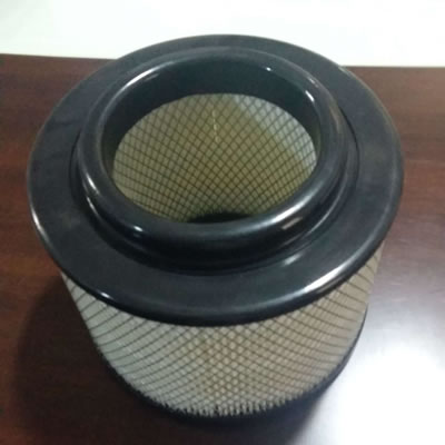 A dust collector filter cartridge with rubber edge is on a desk.