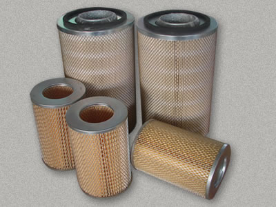 Five dust collector filter cartridges are placed in workshop.
