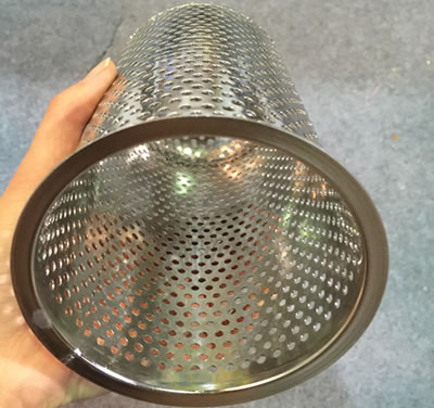 A hand is holding a piece of perforated filter cartridge.