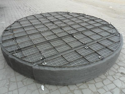 A round metal mist eliminator is divided into six parts on the ground.