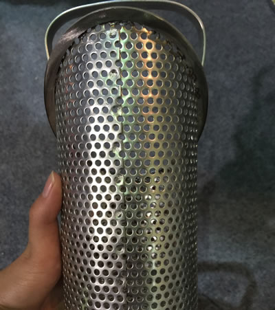 A perforated round cylinder with a handle.