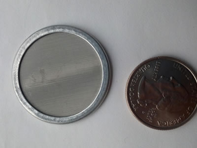 A wrapped edge stainless steel filter disc is beside a metal coin.