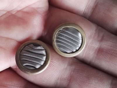 Two pieces of pleated surface filter discs are on a hand.