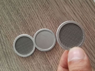Three round filter discs with metal coin in the middle.