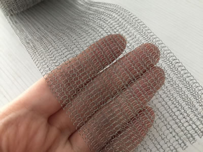 The hand is holding a piece of knitted wire mesh filter and we can see the woven type of the mesh clearly.